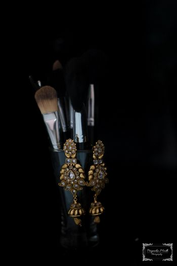 Gold Kundan Earrings Hanging on a Makeup Kit