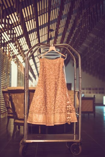 Photo of Dull Gold Bridal Lehenga with Latkans on a Hanger