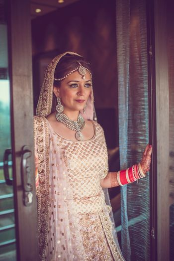 Photo of Bride wearing Cream and Gold Lehenga