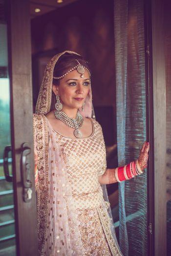 Photo of Bride wearing Cream and Gold Lehenga