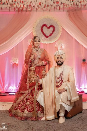 A royal sikh couple posing on their wedding day.