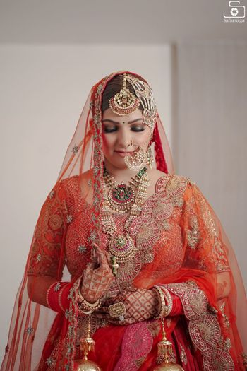 Photo of a bride wearing red lehenga and oversized jewellery.