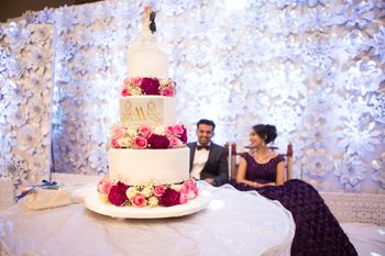 Photo of Three-layered white wedding cake with flowers