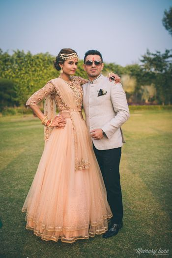 Couple wearing Peach Lehenga and White Bandhgala
