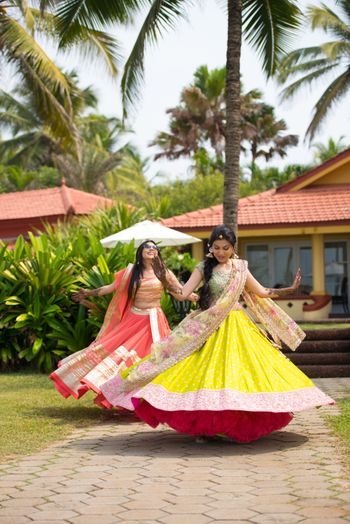 Photo of Twirling Bridesmaids in  Yellow and Pink Lehengas