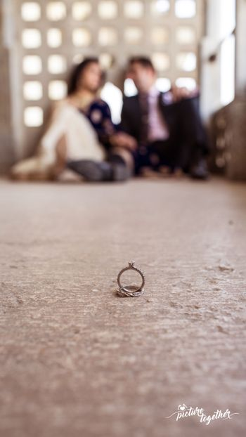 Photo of Engagement Rings in Focus with Couple Out of Focus