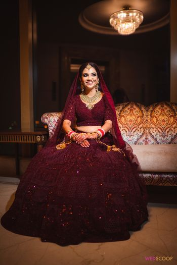 Bride dressed in a deep maroon bridal lehenga.