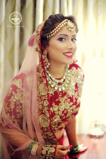 Bride in Red Lehenga and Pastel Pink Dupatta