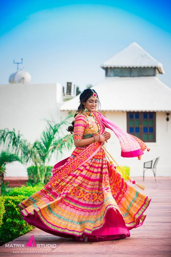 A twirling lehenga shot of the bride in a bright pink lehenga