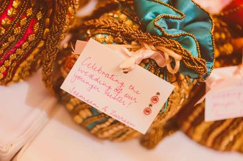Photo of potlis in silk containing bangles mehendi favors