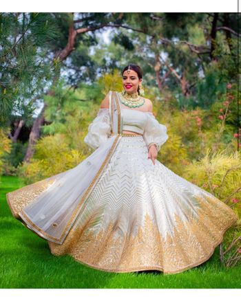 Photo of Bride in a white and golden lehenga