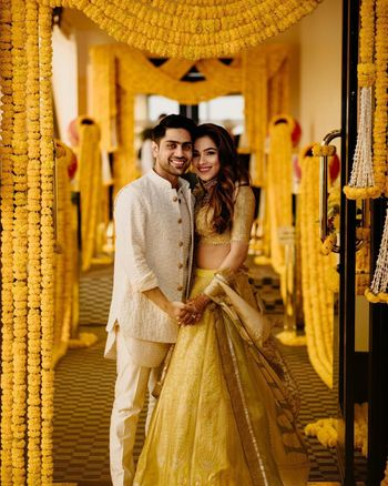 Photo of A bride and groom portrait with genda phool decor in the backdrop