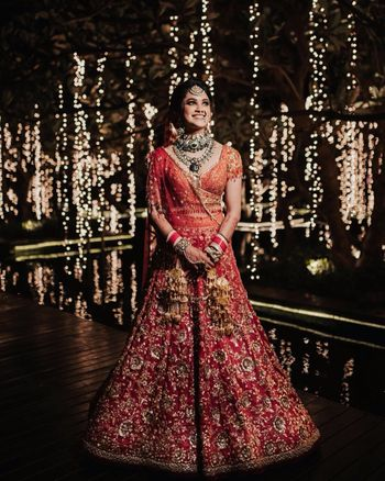 A beautiful orange and red bridal outfit by Tarun Tahiliani