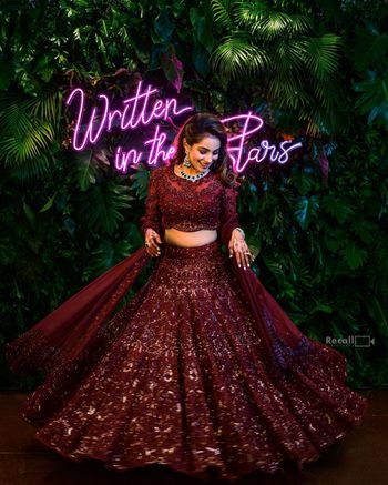 Photo of The bride twirls in a gorgeous maroon lehenga on her sangeet