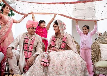 Photo of A cute shot of the couple under a dupatta held by kids