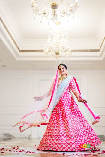 Twirling bride in bright  pink lehenga