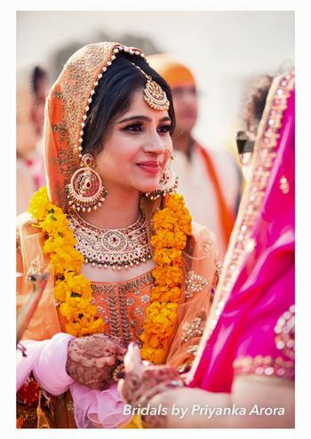 Photo of Bride in Orange Dupatta and Gold Jewelry