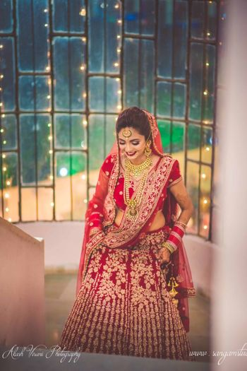 Bride entering in red and gold lehenga