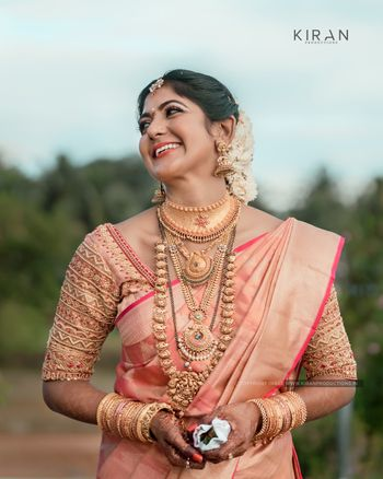 South Indian bride dressed in pink saree on her wedding day