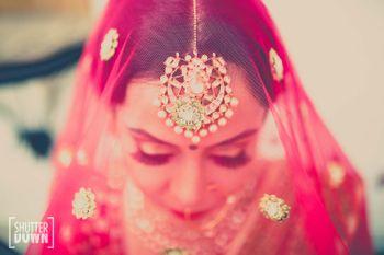 Bride in Hot Pink Veil and Gold Maangtikka