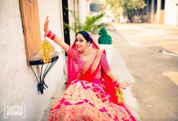 Photo of Fun Bride in Hot Pink Lehenga and Gold Kaleere
