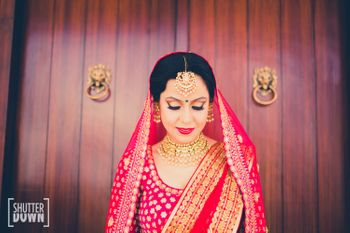 Photo of Candid Bride in Pink and Gold Lehenga