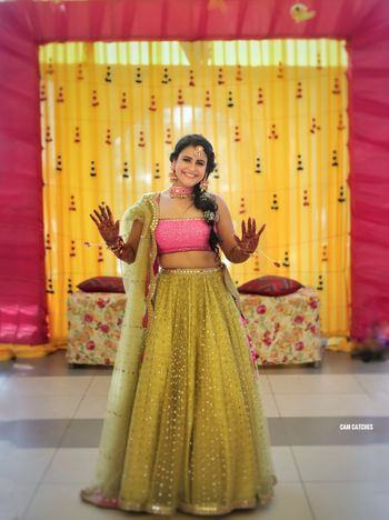 A bride in a light green and pink lehenga for her mehendi