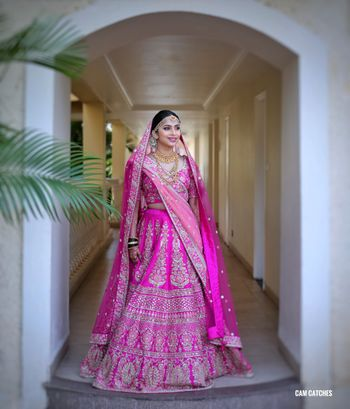 Photo of A bride in a rani pink lehenga for her wedding