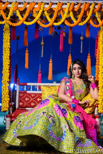 South Indian bride in a multi-colored lehenga posing on a jhoola.