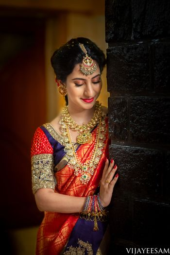 A coy South Indian bride wearing a red and blue saree with temple jewellery