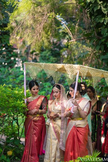 South Indian Bridal Entry under a phoolon ki chaadar with bridesmaids.