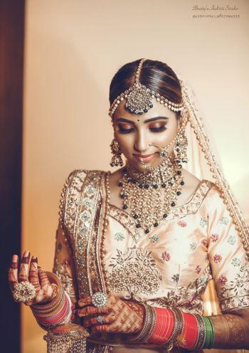 Photo of Candid shot of a bride dressed in a light pink lehenga with contrasting jewellery.