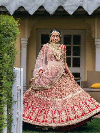 twirling bride shot in a red lehenga with gold work
