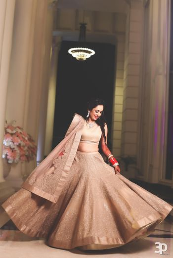 Bride Twirling in Champagne and Gold Light Lehenga