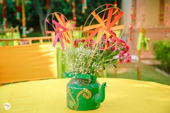 Tea Kettle centrepiece filled with flowers and pinwheels.