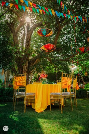 Photo of Yellow table settings and chair decor for an outdoor ceremony.