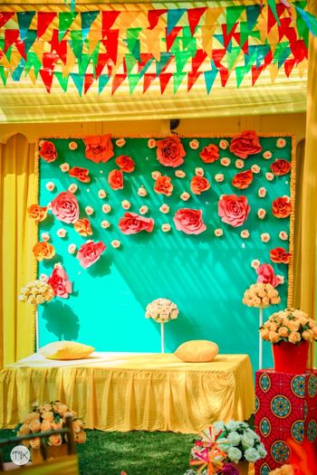 Yellow Mehendi seating with a backdrop decorated with paper flowers.