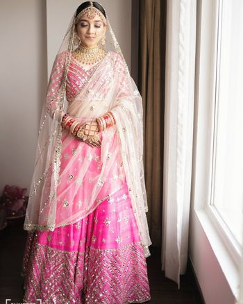 Bride wearing a bright pink lehenga with a white dupatta.