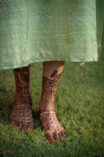 Feet Mehendi design with peacocks and jaalidaar patterns.