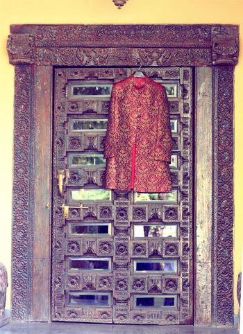 Deep Red Sherwani Hung on Royal Door