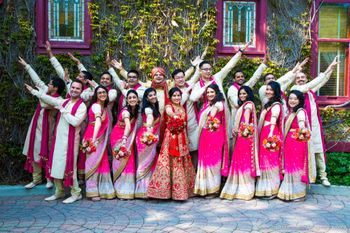 Photo of Bridesmaids and Groomsmen in Pink Posing with Couple