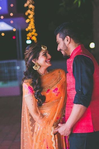Cute couple portrait with bride in orange mehendi lehenga