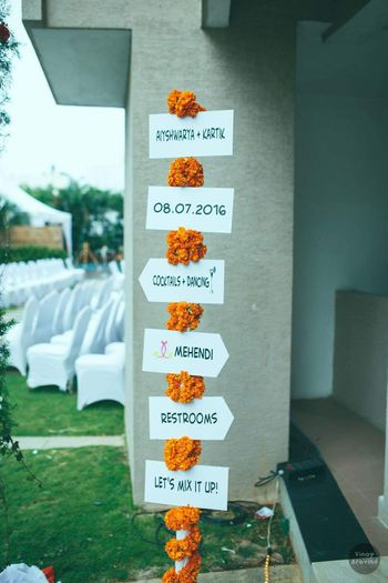 White direction boards with genda phool