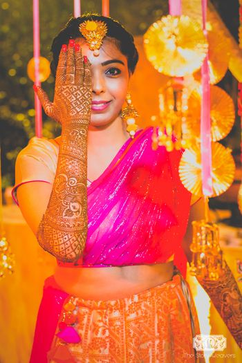 Bride showing off mehendi with quirky mehendi decor
