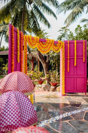 Photo of Mehendi decor with a pink entrance and genda phools.