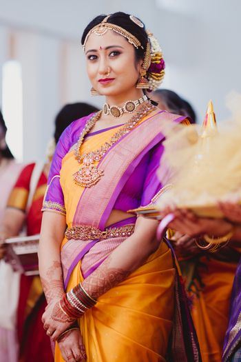South Indian bride wearing an orange saree with a purple blouse.