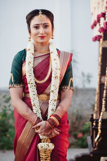 South Indian bride dressed in a maroon saree with a dark green blouse.