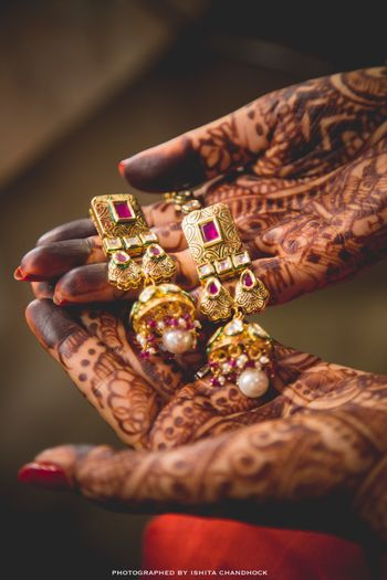 Bride Holding Pink and Gold Polki Danglers