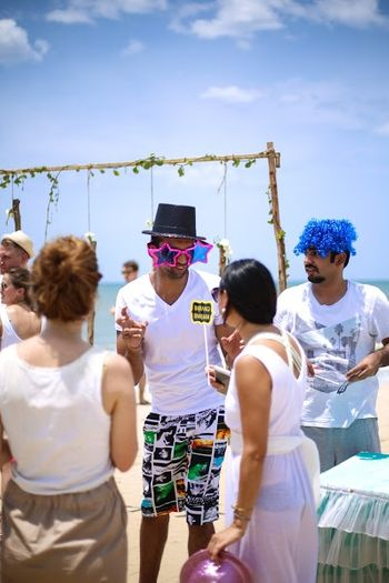 Photo of Fun Beach Wedding Party Photo with Props