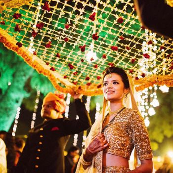 Bride in Gold Lehenga Entering Under Phoolon ki Chadar